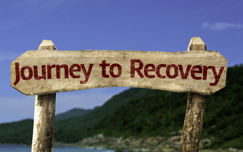 Journey to Recovery wooden sign with a beach on background
