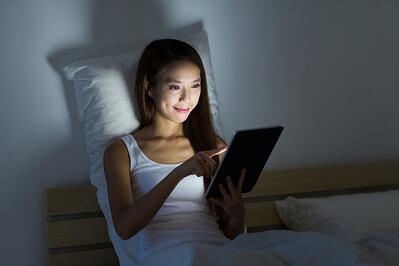 Woman working overnight with tablet pc and sitting on bed