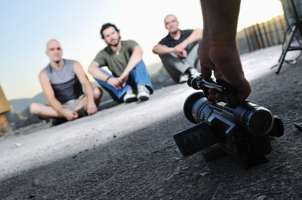 three young business man siting on ground creating promotional videos
