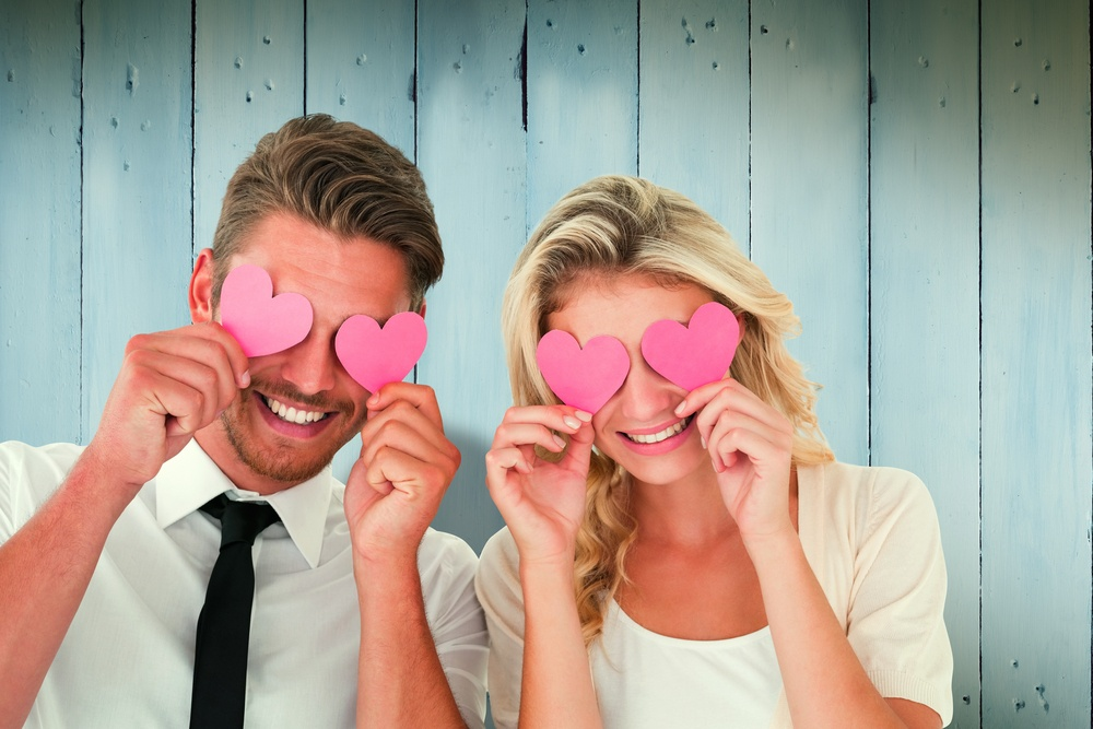 Attractive young couple holding pink hearts over eyes against wooden planks
