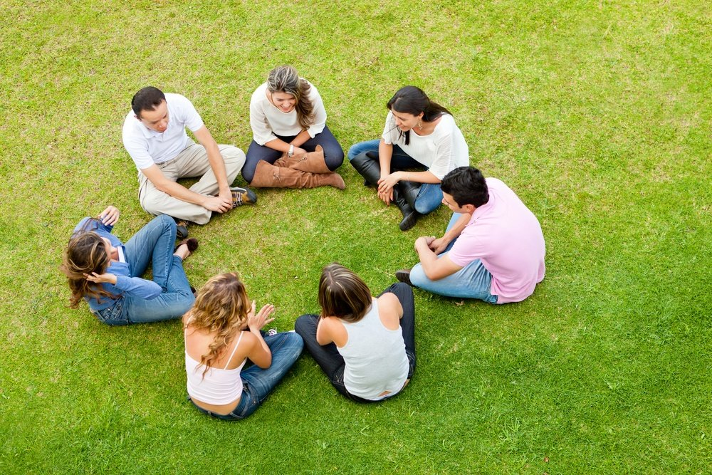 Group of friends sitting down in a circle outdoors