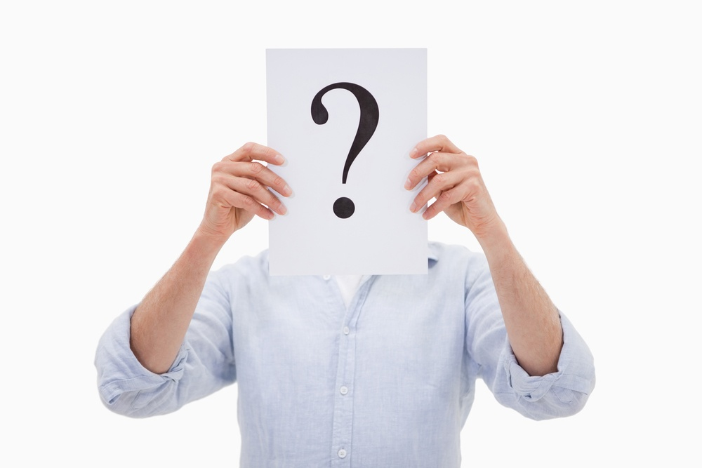 Portrait of a man hiding his face behind a question mark against a white background.jpeg